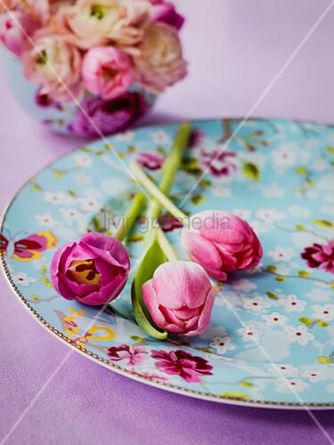 Pinkfarbene Tulpen auf hellblauem Teller mit Blütenmotiven