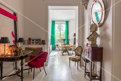 Bust on console table below mirror on wall, red upholstered chair and antique table in anteroom