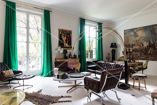 Brown leather sofa set and Italian designer lamp in living room with huge painting in dining area in background