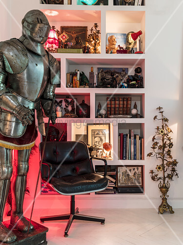 Suit of armour and leather chair in front of shelves holding eclectic collection of items