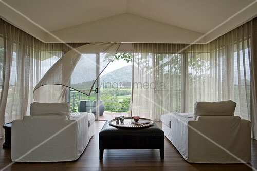 Two couches with white loose covers and ottoman in relaxation room with glass walls and open balcony door