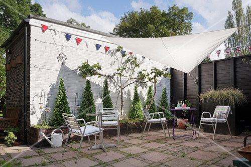 Metal chairs and tables on paved terrace with bunting and awning