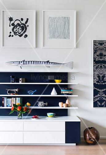 Deko auf weißem Regal mit schwarzer Rückwand im Wohnzimmer