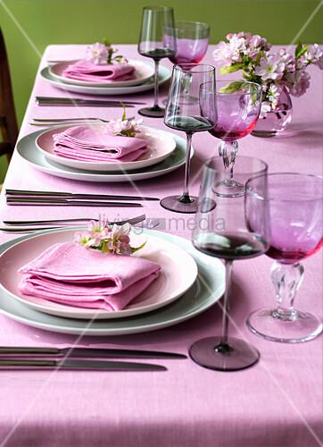 Gedeckter Esstisch mit pinkem Tischtuch und Stoffservietten