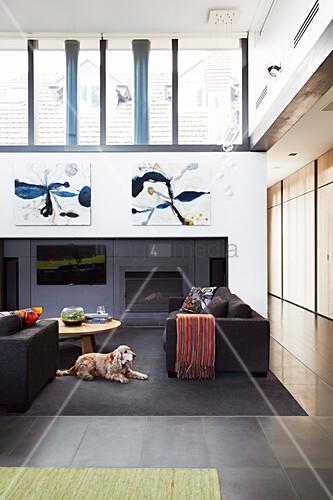 Loungebereich mit schwarzer Polstergarnitur, Kamin und Fernseher in hohem Raum