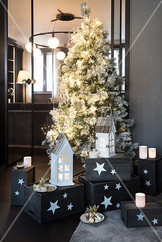 Weiss geschmückter Weihnachtsbaum mit Windlichtern und Laternen auf grauen Holzkisten