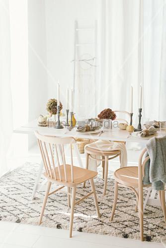 Herbstlich gedeckter Tisch in hellem Wohnraum