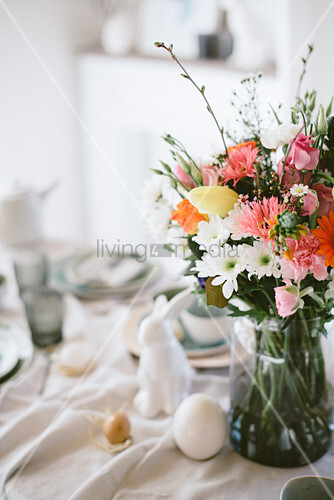 Vase of colourful flowers on Easter breakfast table