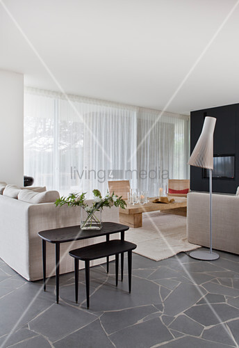 Pale sofa set and black side tables in open-plan interior