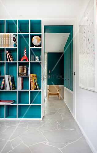Turquoise fitted shelving next to open doorway leading into adjoining room with continuous stone floor