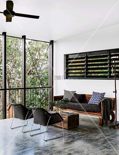 Holzsofa, Armlehnstühel und alte Truhe als Couchtisch in offenem Raum mit Betonboden