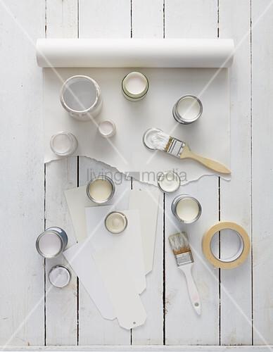 Offene Farbtöpfe mit verschiedenen Weiß-Tönen auf einer Rolle Papier