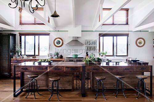 Kücheninsel mit Schubladen aus recyceltem Holz und Vintage Barhocker in offener Küche