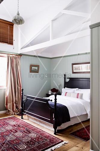 Schlafzimmer mit Holzbett in umgebauter Scheune