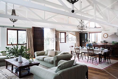 Offener Wohnraum mit Polstergarnitur, Essbereich und Küche in umgebauter Scheune