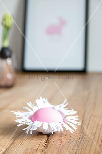 Easter egg in handmade paper nest on wooden surface
