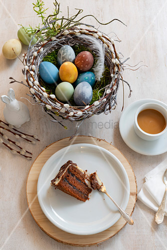 Easter eggs in handmade pussy willow Easter nest, piece of cake and cup of coffee