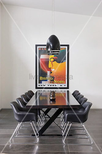 Elegant black table and black shell chairs below black pendant lamps and in front of framed poster on wall