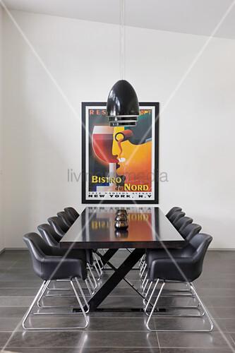 Eleganter, schwarzer Tisch mit schwarzen Schalenstühlen, darüber schwarze Pendelleuchten, an Wand gerahmtes Plakat