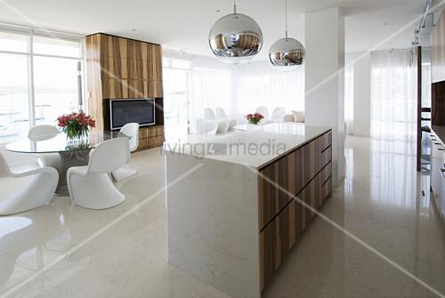 Kücheninsel aus Marmor, weiße Designerstühle um Glastisch und Fernsehregal in offenem Wohraum