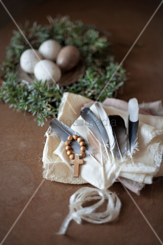Feathers and cross on wooden beads on white cloth in front of speckled eggs on pewter plate in Easter nest