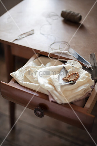 Feathers and cross on wooden beads on white cloth in open drawer