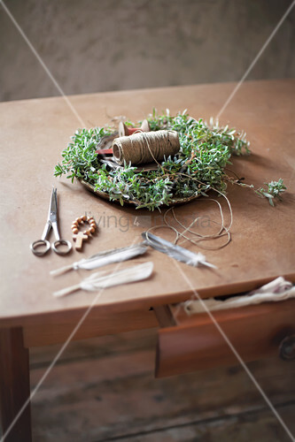 Handmade chickweed Easter nest with twine, wooden beads, scissors and feathers on wooden table