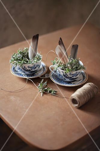 Osternest mit Federn in blau-weißen Porzellantassen