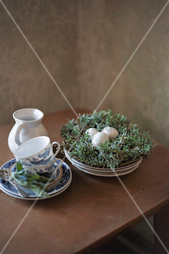 Breakfast crockery next to speckled eggs in Easter nest