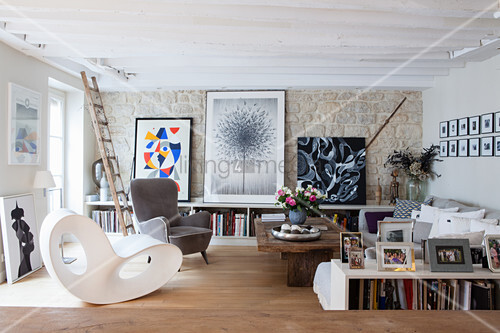 Artistic mixture of styles in living room with stone wall
