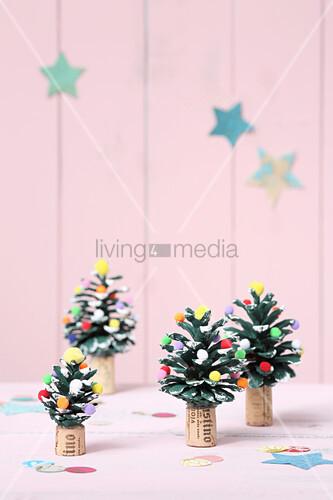 Mit Pompons dekorierte und bemalte Zapfen als Weihnachtsbäume