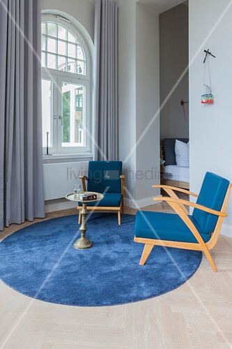 Blue armchairs and side table on round