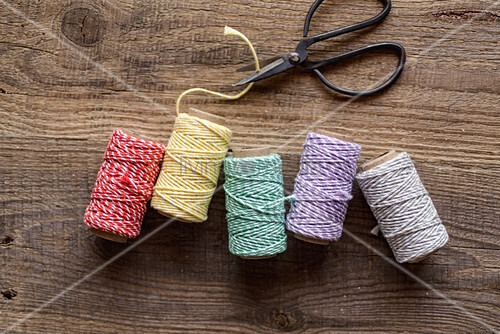 Reels of colourful thread and scissors on wooden surface