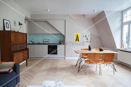 Schlichte Einbauküche, Essbereich, Sofa und Bett in offenem Wohnraum