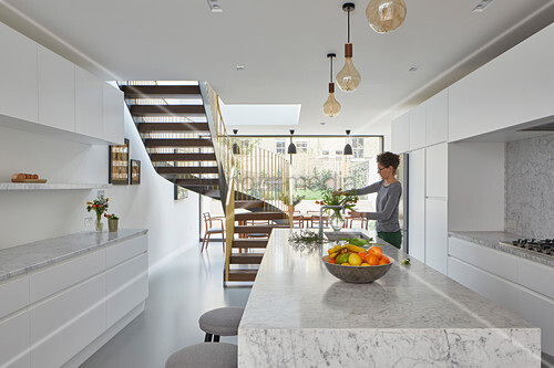 White, marble, minimalist kitchen with view into dining room