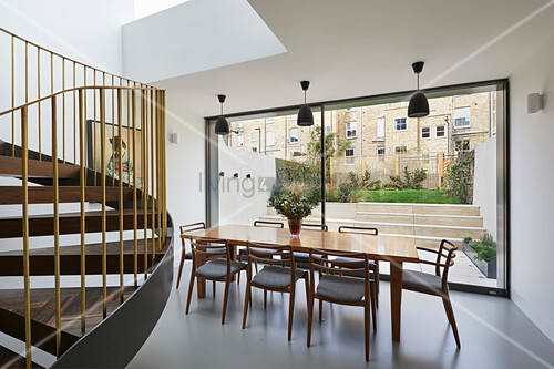 Minimalist dining room with view of garden through glass wall