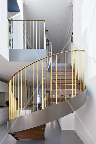 Spiral staircase with gold balustrades in open-plan interior