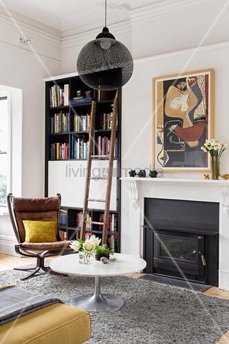 Coffeetable und Klassikerstuhl vor Kamin und Bücherregal mit Leiter im Wohnzimmer