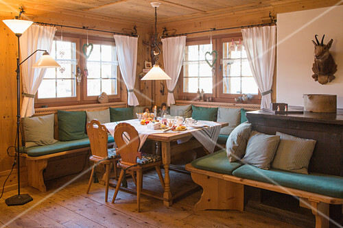 Corner bench with green cushions and scatter cushions in rustic farmhouse parlour