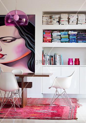 Esstisch mit Schalenstühlen vor Bücherregal und Kunstwerk