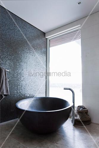 Freistehende ovale Badewanne vor schimmernder Mosaikwand