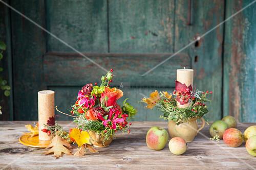 Herbstlich dekorierte Kerzen und Blumenschmuck