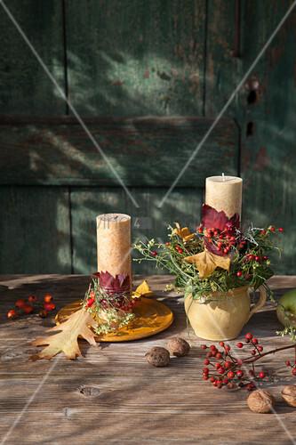 Herbstlich dekorierte Kerzen auf Teller und im Krug