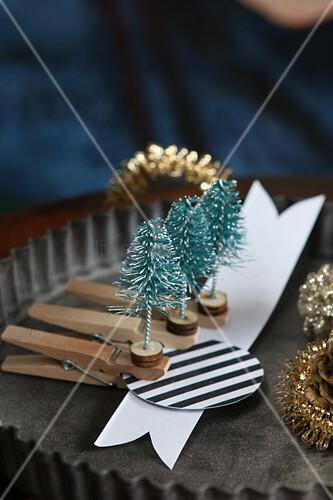 Handmade miniature Christmas-tree decorations on pegs