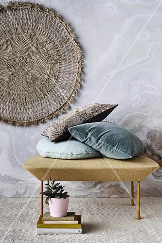 Kissen auf Pouf, davor Bücherstapel und Zimmerpflanze