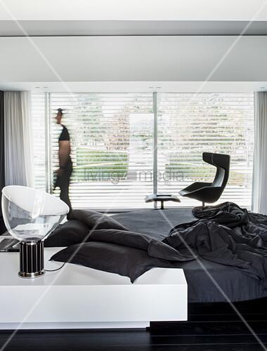 Minimalistischer Schlafraum in Schwarz und Weiß mit Designermöbeln, Person vor Fenster