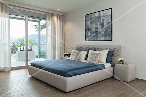 Bed with upholstered frame in minimalist bedroom in grey and blue