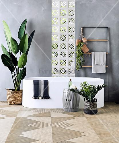 Frei stehende Badewanne, Handtuchtrockner und Zimmerpflanzen im Bad