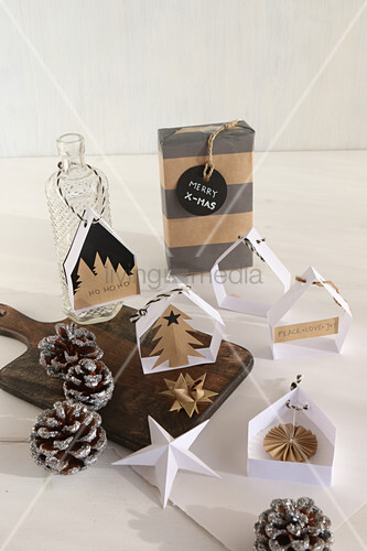 Handcrafted Christmas decorations: small paper houses for hanging up