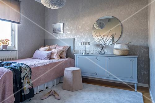 Romantisches Schlafzimmer in Grau und Rosa mit altem Sideboard